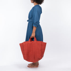 THE REGULAR Quilt Dress in regular wash denim. Side view shows midi length, puffed sleeves.  Worn with hand held Quilt Tote in brick linen.