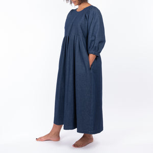 THE REGULAR Quilt Dress in dark rinse wash denim. Side view shows midi length, puffed sleeves and unbelted.  Worn with hands in side pocket.