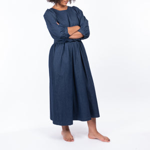 THE REGULAR Quilt Dress in dark rinse wash denim. Front, side view shows midi length, puffed sleeves, quilted bodice and belted at waist.  Model has arms folded.