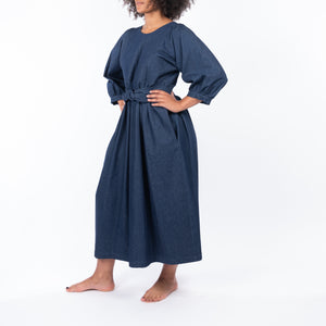 THE REGULAR Quilt Dress in dark rinse wash denim. Front, side view shows midi length, puffed sleeves, quilted bodice and belted at waist.  Model has hands on hips.