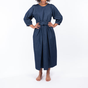 THE REGULAR Quilt Dress in dark rinse wash denim. Front view shows midi length, puffed sleeves and belted at waist.  Model has hands on hips.