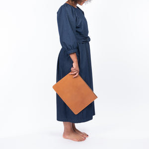 THE REGULAR Quilt Dress in dark rinse wash denim. Side view shows midi length, puffed sleeves, quilted bodice and belted at waist.  Worn with tan leather Folio style clutch bag.