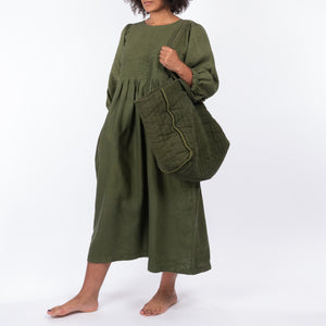 THE REGULAR Large Quilt Tote in olive green garment dyed linen fabric, worn shoulder tote style, with the Quilt Dress worn unbelted.
