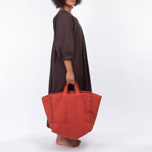 THE REGULAR Large Quilt Tote in brick red, garment dyed linen fabric.   Large quilted panels are bound together creating exposed seams. Model wears bark brown linen Quilt Dress and carries Tote bag by it's shorter grab handle.