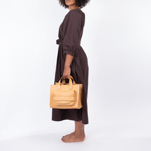 THE REGULAR light tan 'blonde' leather Pioneer Tote bag. Worn with midi length, bark brown linen Quilt Dress.