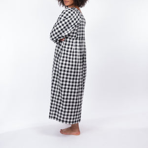 THE REGULAR Quilt Dress in black and white gingham checked cotton. Midi length, shown with puffed sleeves, quilted back bodice and unbelted at waist.