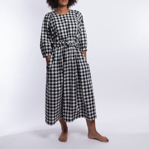 THE REGULAR Quilt Dress in black and white gingham checked cotton. Midi length, shown with puffed sleeves, quilted front bodice and belted at waist. Model wears with hands in large side pockets.
