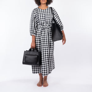 THE REGULAR Quilt Dress in black and white gingham checked cotton. Midi length, shown with puffed sleeves, quilted front bodice and belted at waist. Model holding medium Pioneer Tote and wearing large Pioneer Tote as a shoulder bag.  Both in black leather.