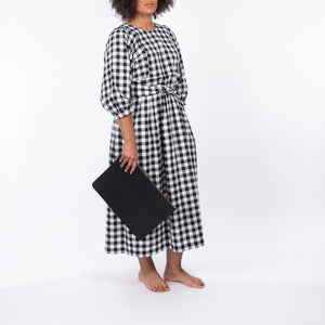 THE REGULAR Quilt Dress in black and white gingham checked cotton. Midi length, shown with puffed sleeves, quilted front bodice and belted at waist. Model holding black leather Folio clutch bag..