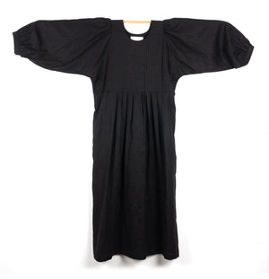 THE REGULAR Quilt Dress in black linen. Midi length, shown with puffed sleeves outstretched from quilted front bodice and unbelted at waist.