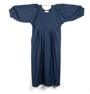 THE REGULAR Quilt Dress in dark rinse wash denim. Midi length, shown with puffed sleeves outstretched from quilted front bodice.