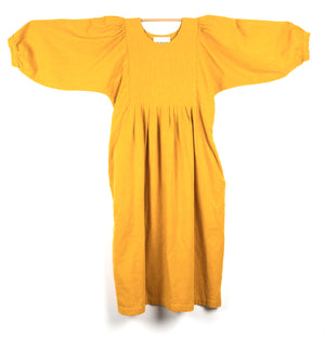 THE REGULAR Quilt Dress in mustard garment dyed linen. Midi length, shown with puffed sleeves outstretched from quilted front bodice and unbelted at waist.