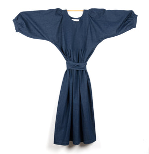 THE REGULAR Quilt Dress in dark rinse wash denim. Midi length, shown with puffed sleeves outstretched from quilted front bodice and belted at waist.
