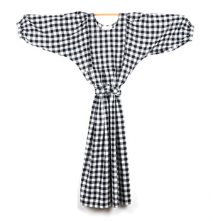 THE REGULAR Quilt Dress in black and white gingham cotton. Midi length, shown with puffed sleeves outstretched from quilted front bodice and belted at waist.