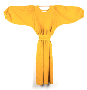 THE REGULAR Quilt Dress in mustard, yellow garment dyed linen. Midi length, shown with puffed sleeves outstretched from quilted front bodice and belted at waist.