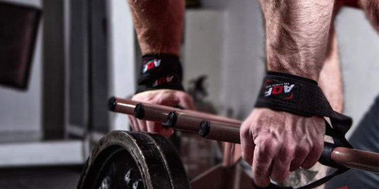 Wrist straps being used to pull weight in the gym