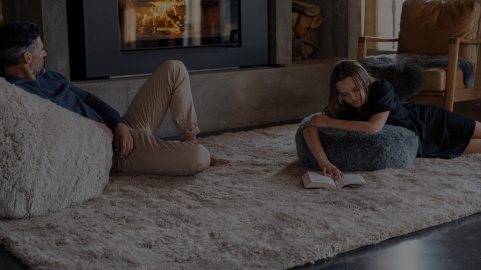 Girl lying on a wool floor rug with her feet up on a sheepskin footstool