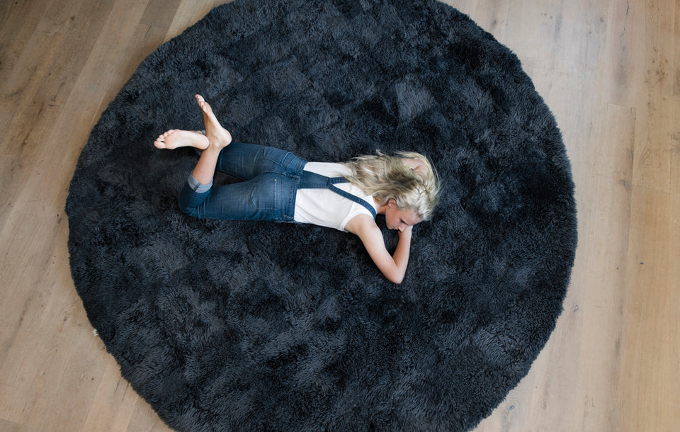 Girl lying on natural colored sheepskin rug wearing denim overalls