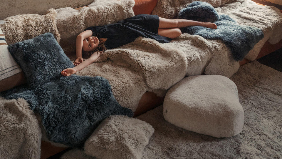 Large sheepskin rug on a white bench seat in a modern interior setting
