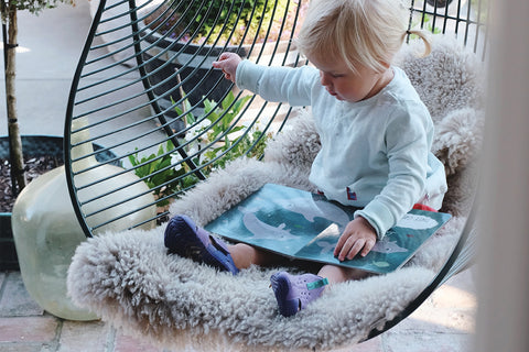 child on wire hanging chair with sheepskin rug cover