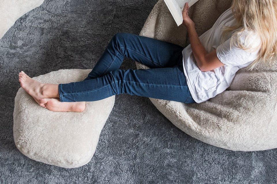 Girl lying on a long wool sheepskin bean bag chair reading a book with her feet up on a sheepskin footstool