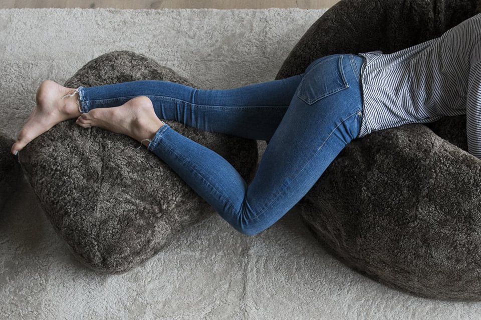 Girl lying on a sheepskin Bean Bag chair with her feet up on a sheepskin footstool