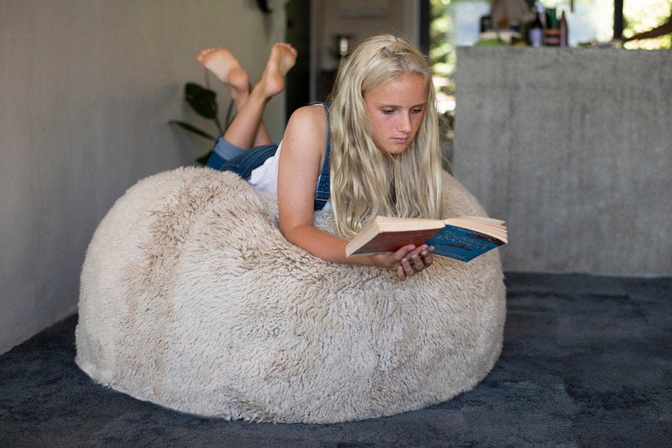 Girl lying on a long wool sheepskin bean bag chair reading a book