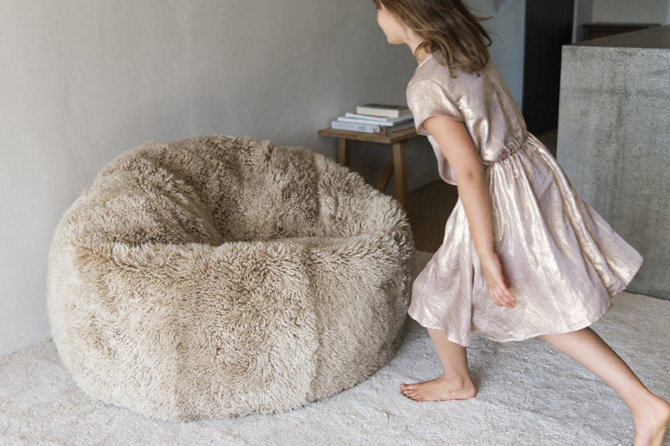 Girl running towards a natural coloured long wool sheepskin bean bag chair