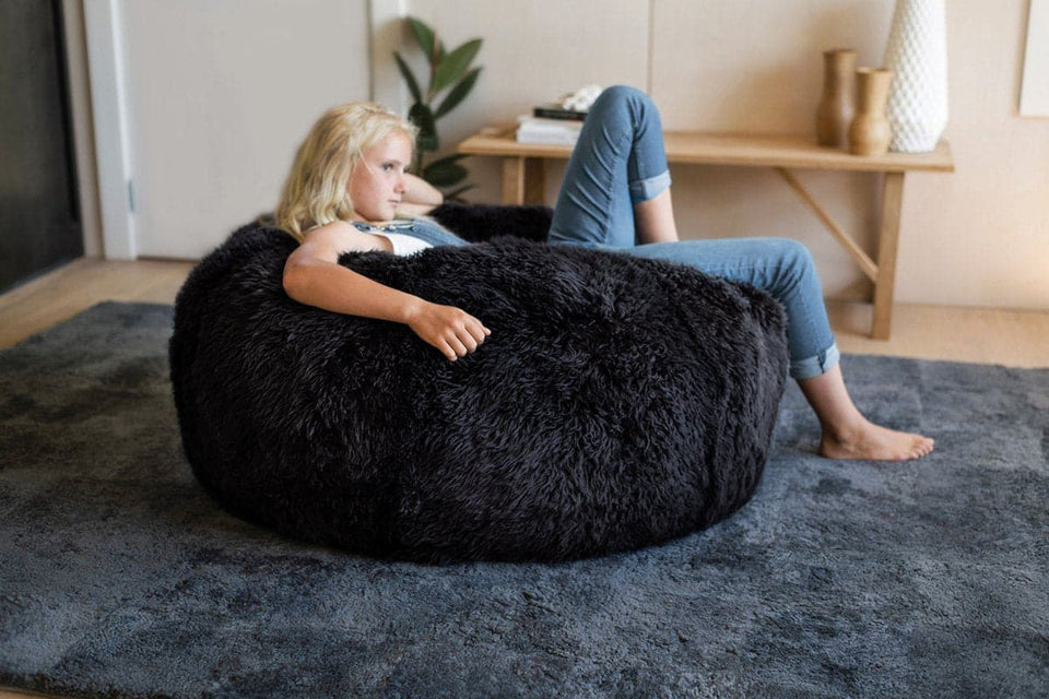 Girl relaxing on a long wool sheepskin bean bag chair