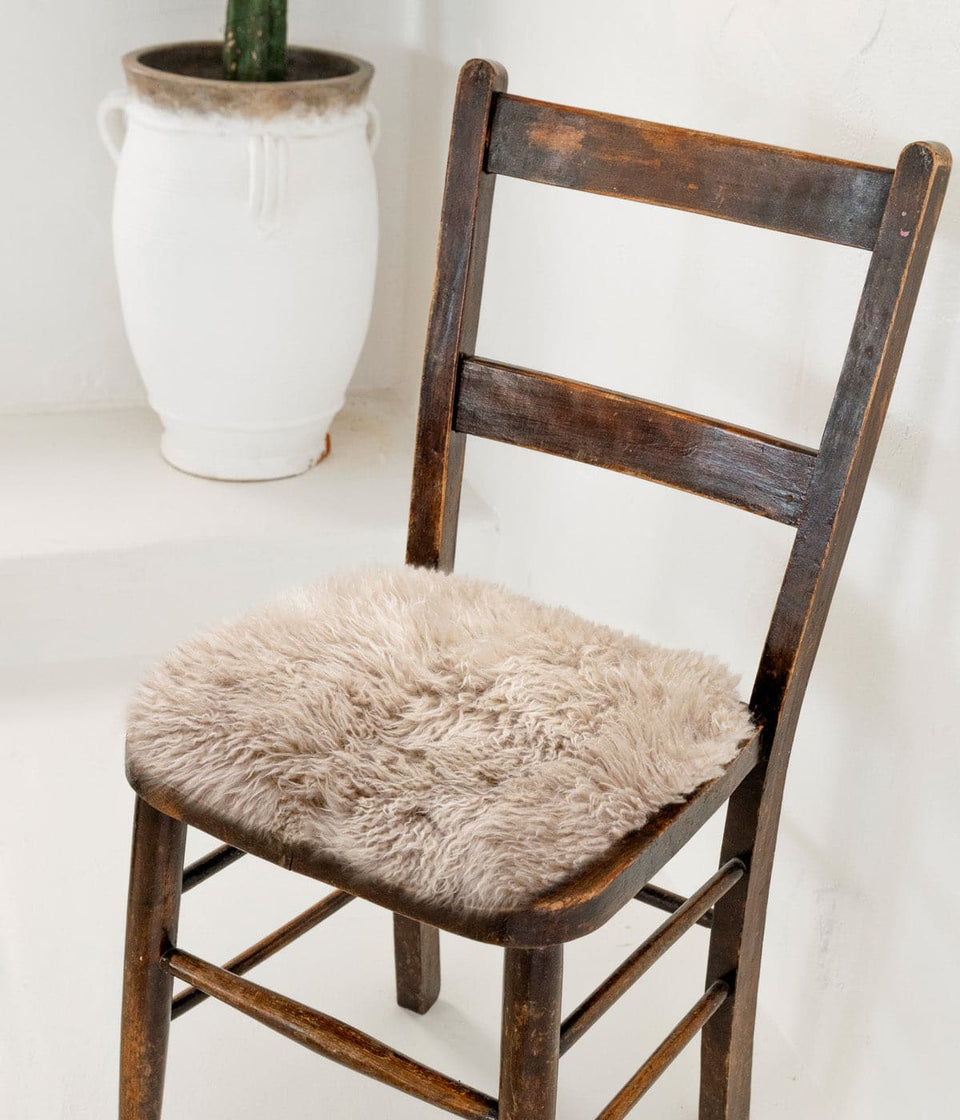 Long wool sheepskin seat cover on a wooden chair