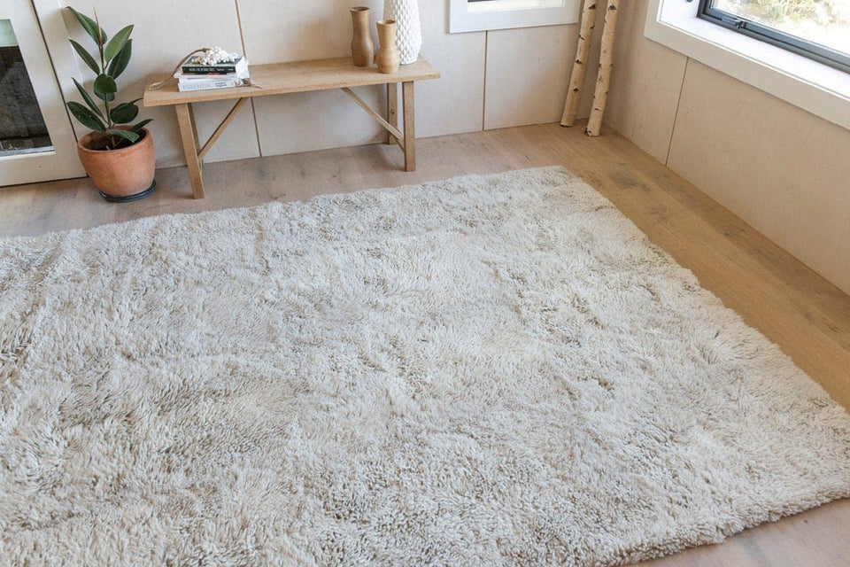 Natural coloured rectangular shaped sheepskin wool floor rug in a minimalist interior