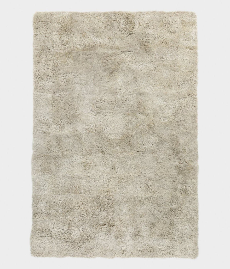 Overhead of a natural coloured rectangular sheepskin wool floor rug