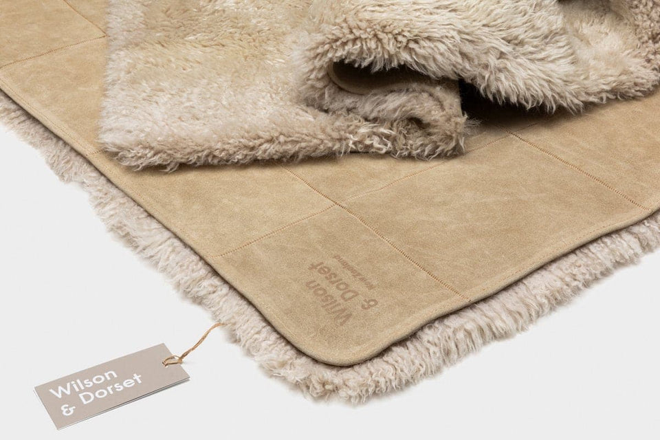 Sheepskin wool floor rug with folded edge showing the suede backing