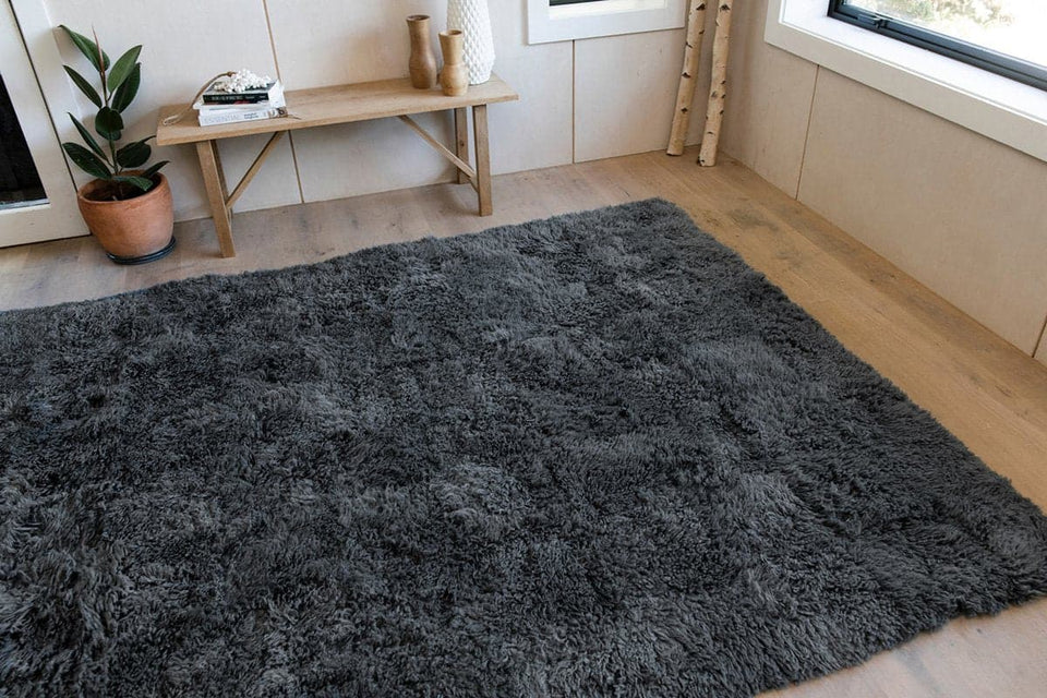 Grey rectangular shaped sheepskin wool floor rug in a minimalist interior
