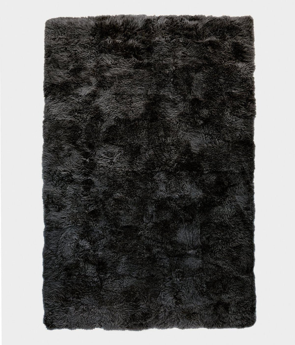 Overhead of a dark grey rectangular sheepskin wool floor rug