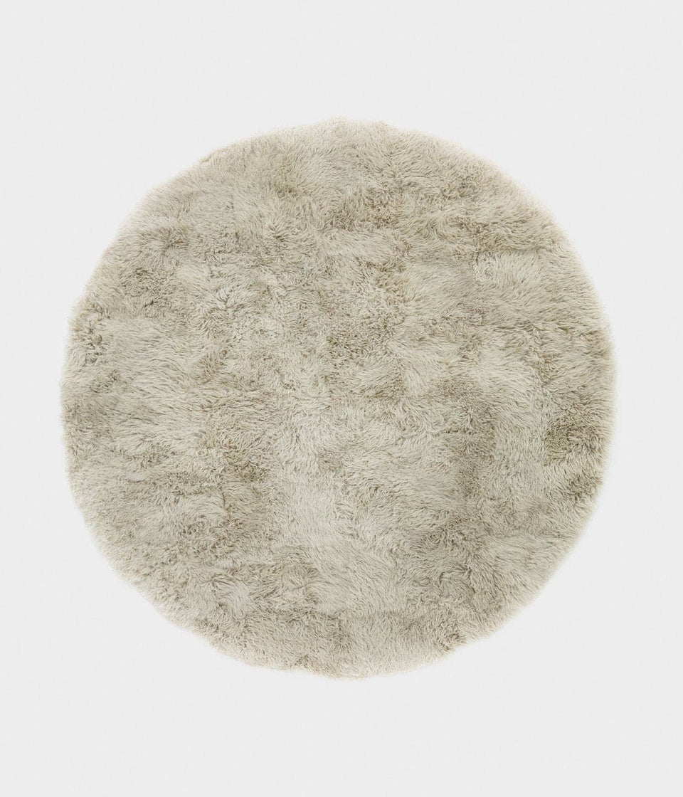 Overhead of a natural colored round sheepskin wool floor rug