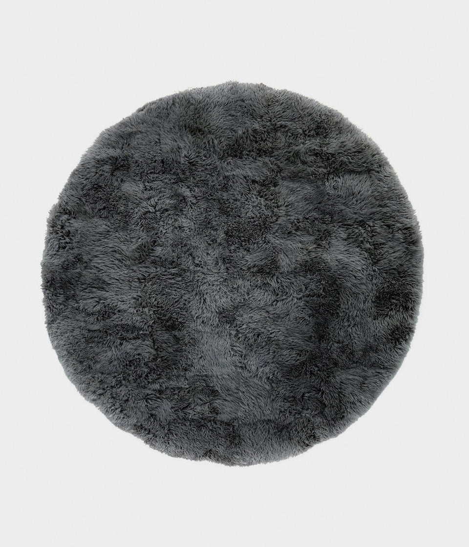 Overhead of a round grey sheepskin wool floor rug