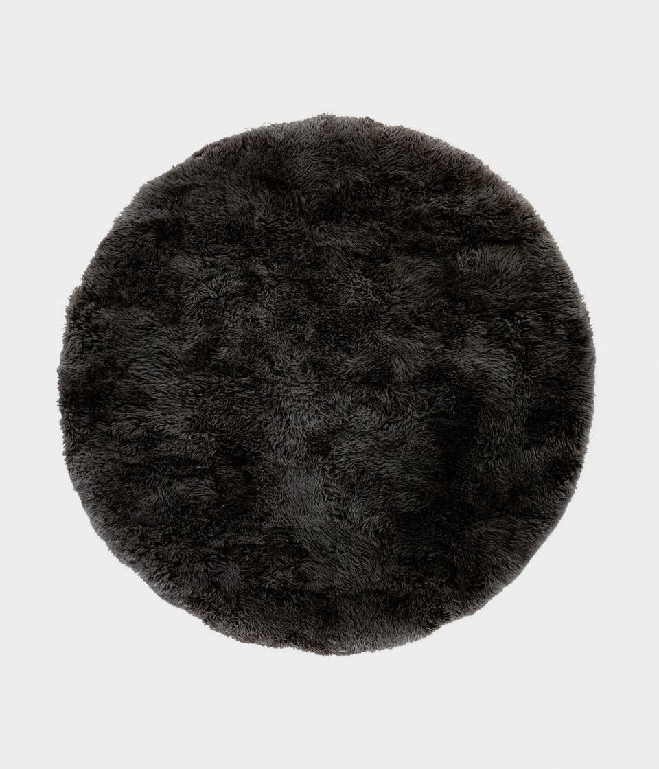 Overhead of a dark grey round sheepskin wool floor rug