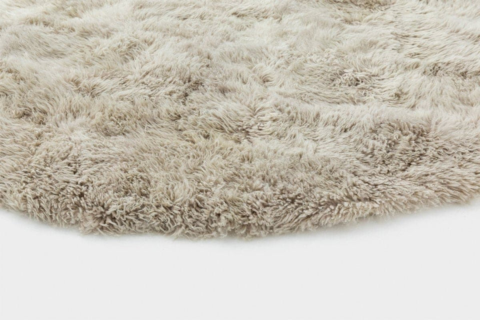 Closeup on the edge of a round sheepskin wool floor rug