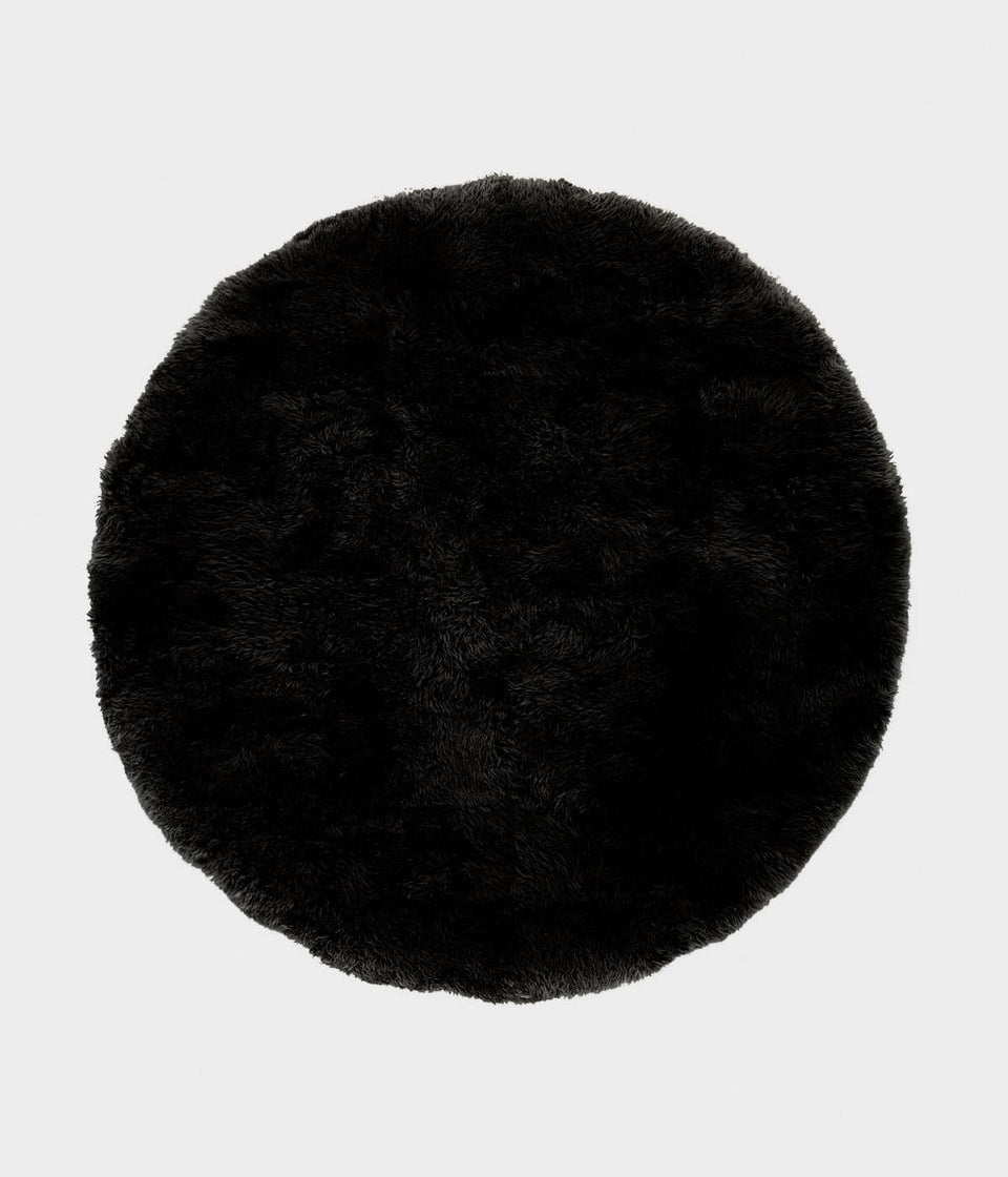 Overhead of a black round sheepskin wool floor rug