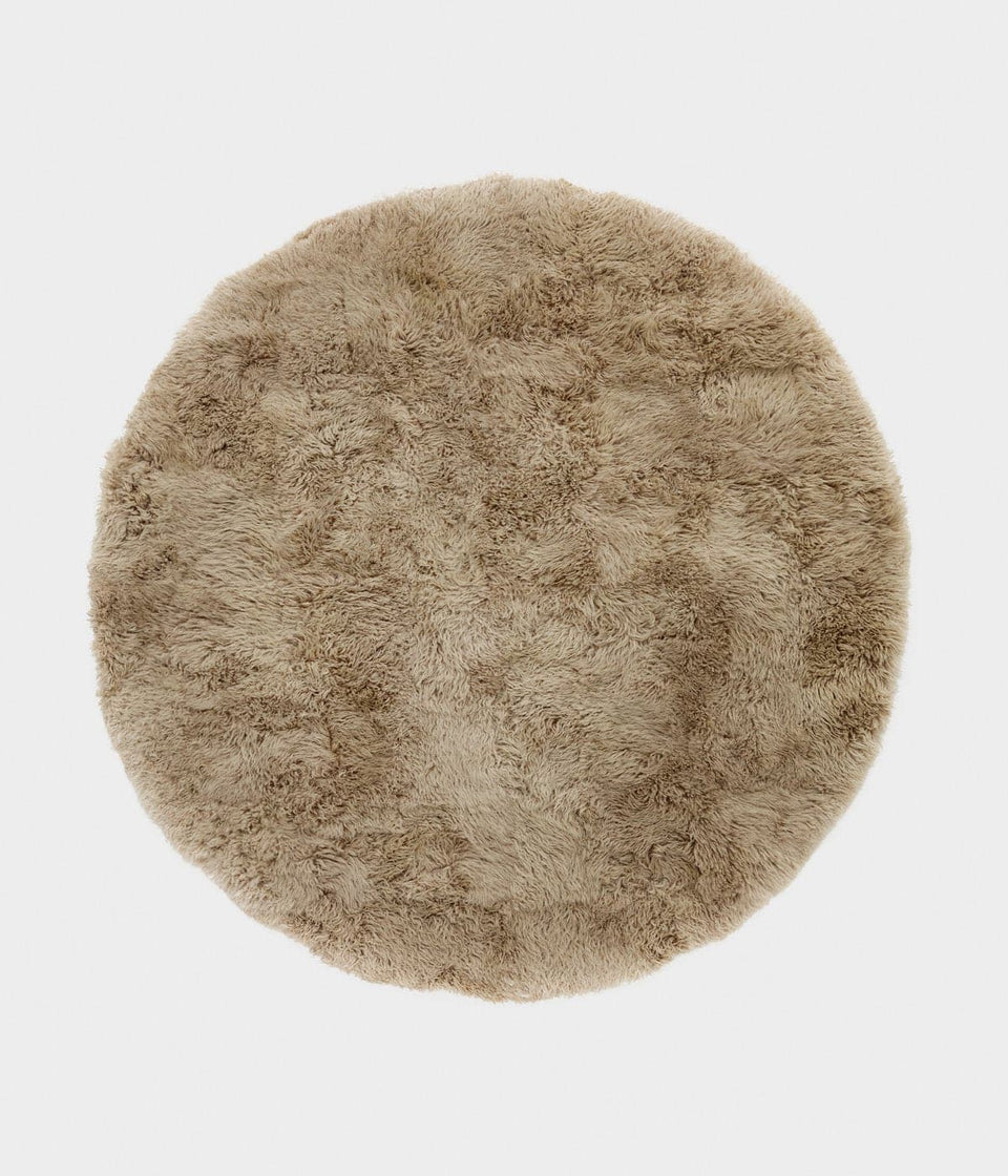 Overhead of a natural coloured round sheepskin wool floor rug
