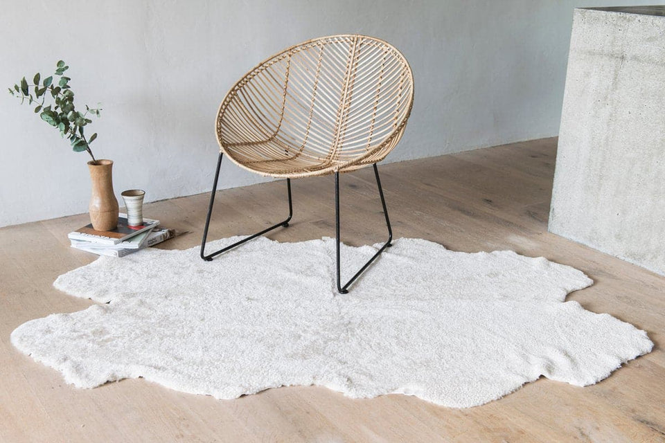 Short wool sheepskin rug on the floor under a cane chair