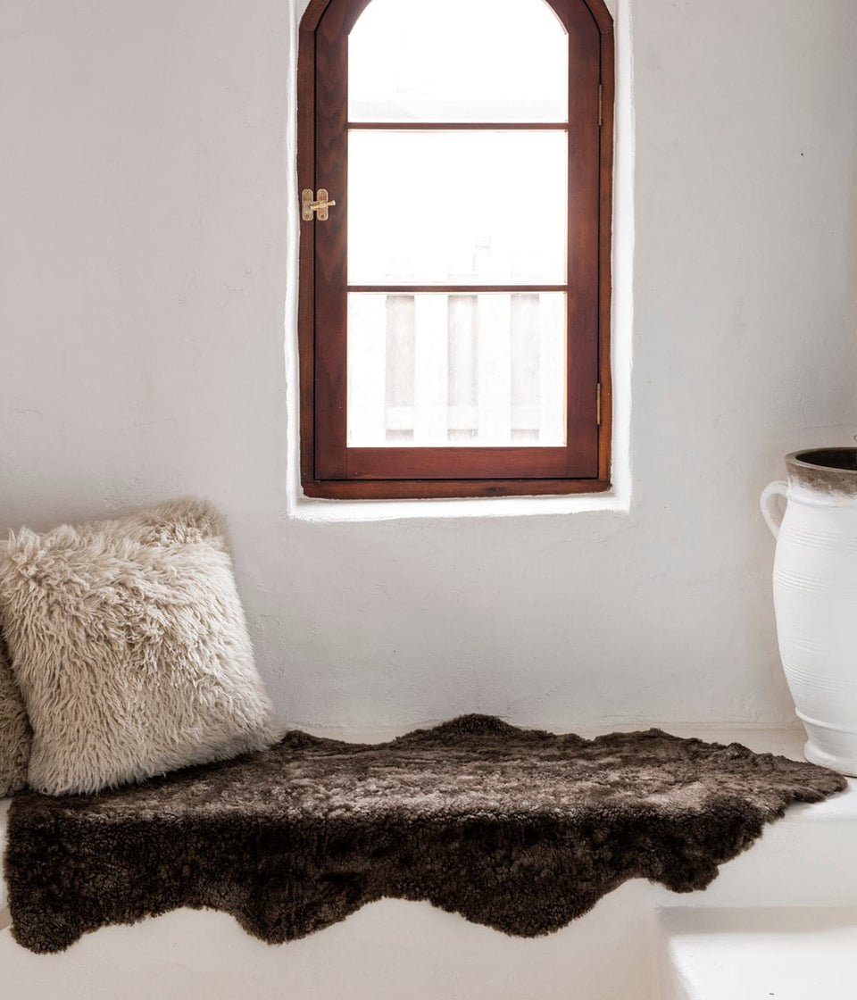 Short wool sheepskin rug on white window seat