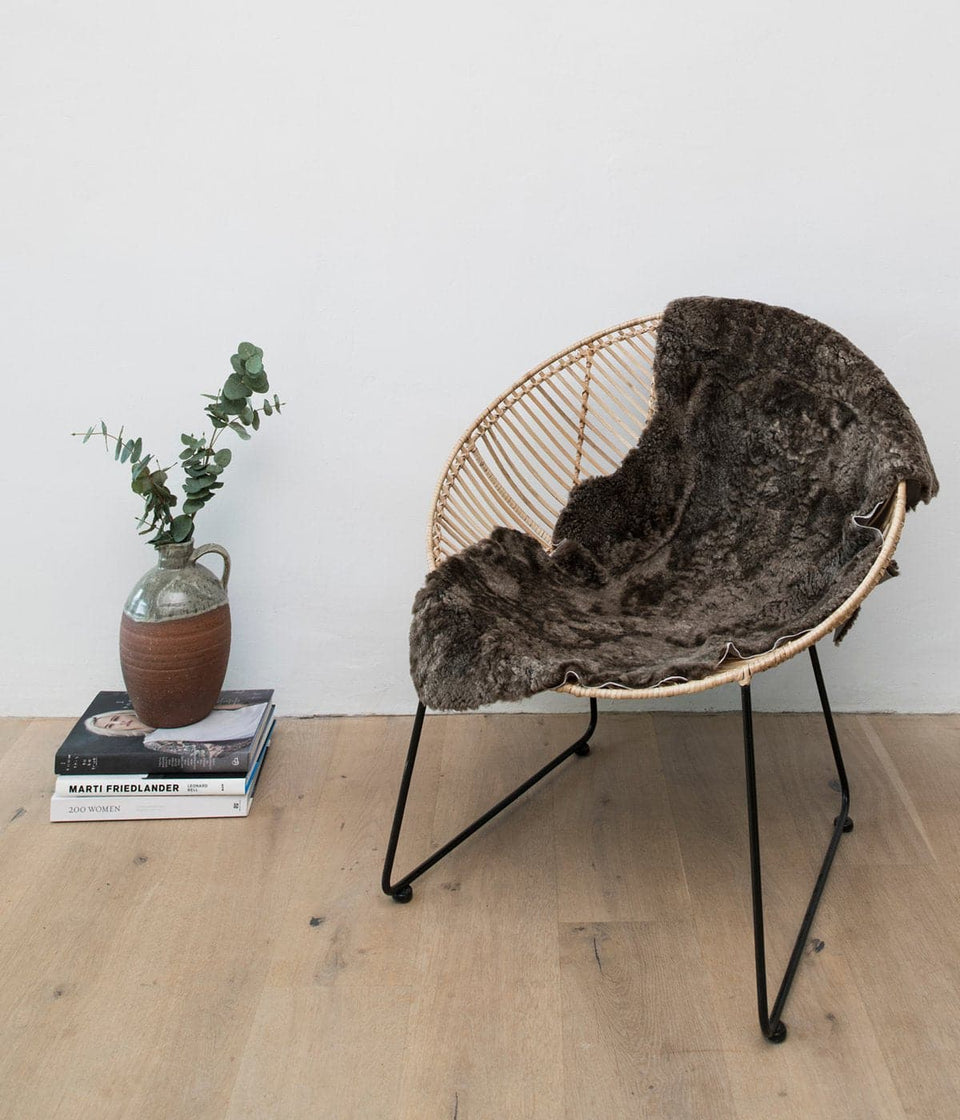 Short wool sheepskin rug on cane chair