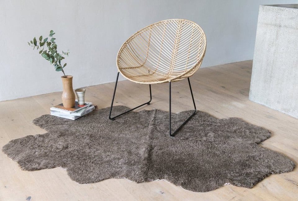 Short wool sheepskin rug on wooden floor under a cane chair