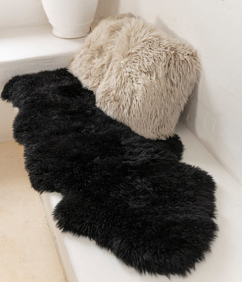 Black long wool sheepskin rug and sheepskin cushions in a minimalist interior