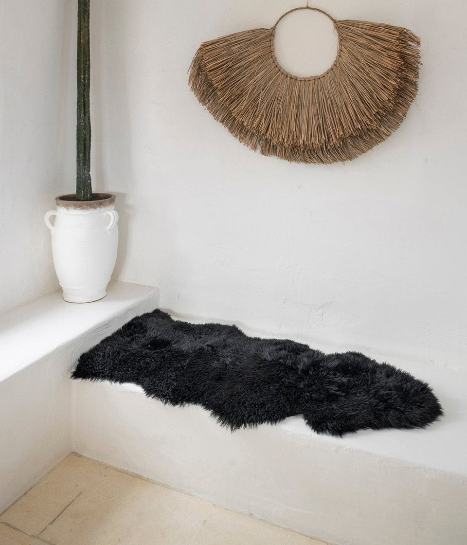 Dark grey new zealand sheepskin rug on white bench seat