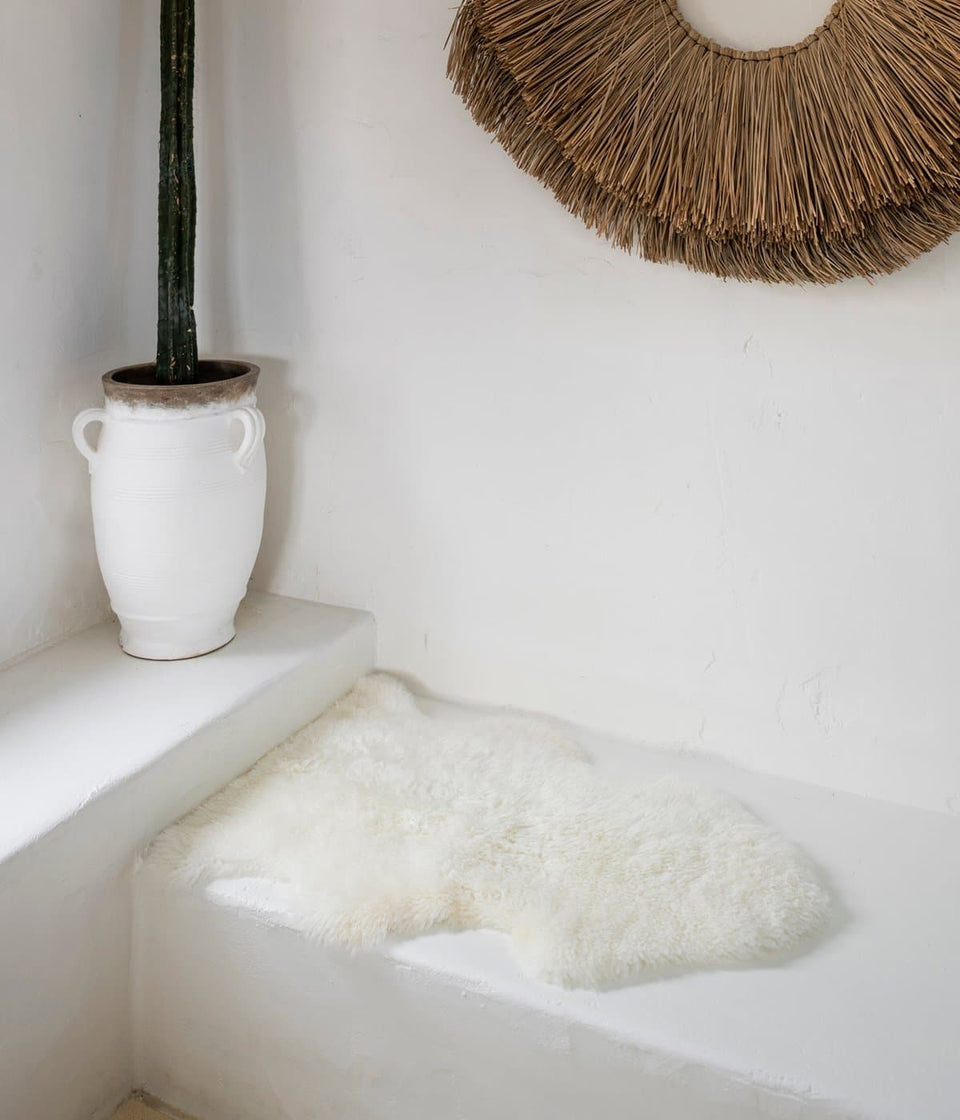 White long wool sheepskin rug on bench seat