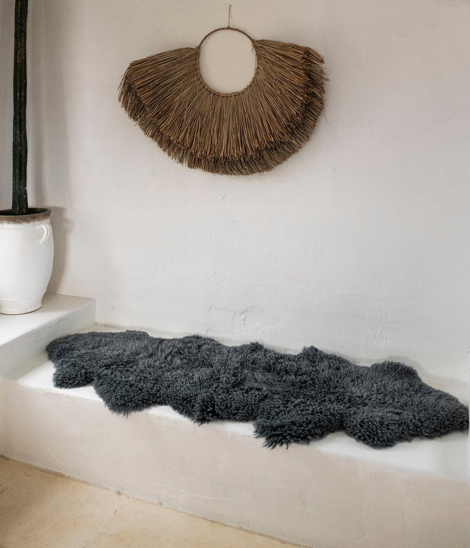 Grey sheepskin rug on white bench seat