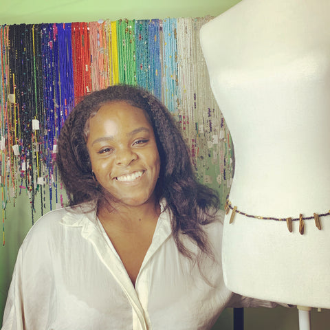 Black female entrepreneur smiling with waistbeads